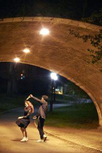 A couple dancing under a bridge