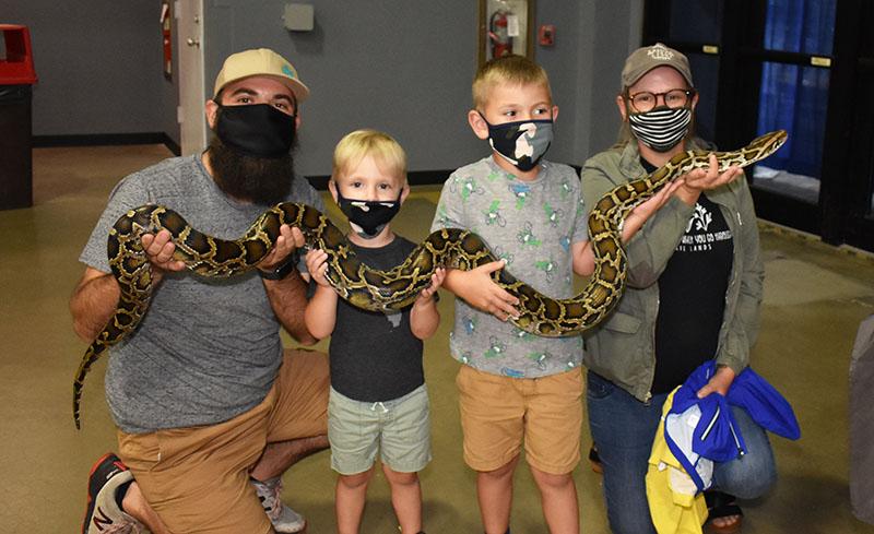 Image of family holding huge python